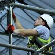 Scaffold operator working on scaffolding wearing PPE on a safe site